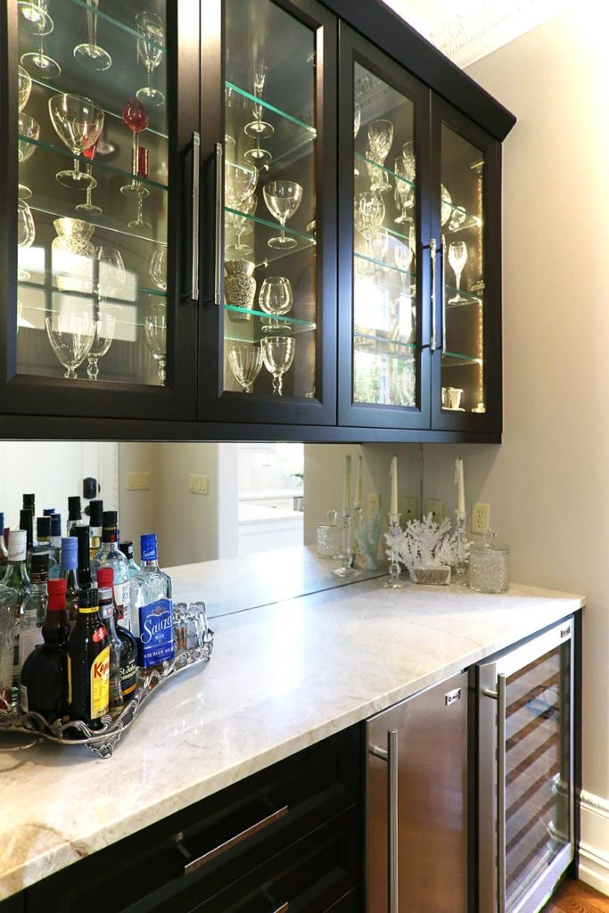 Tulsa kitchen bar space with rich dark brown cabinets, under counter stainless Sub-Zero ice and wine/beverage refrigerator and mirror backsplash
