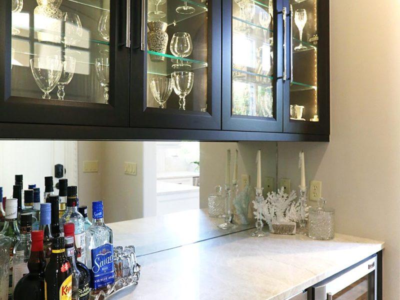 Tulsa kitchen bar space with rich dark brown cabinets, under counter stainless Sub-Zero ice and wine/beverage refrigerator and mirror backsplash