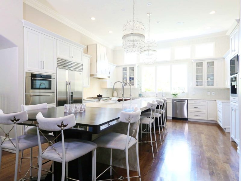 Timeless elegant large south Tulsa kitchen with large island, Galley Workstation, stainless appliances, wood floors and white cabinets