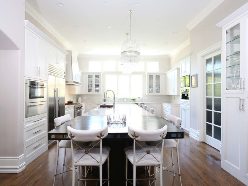 Timeless elegant large south Tulsa kitchen featuring a large island, Galley Workstation, Wolf appliances refinished wood floors, white cabinets, island chandeliers and wood table seating