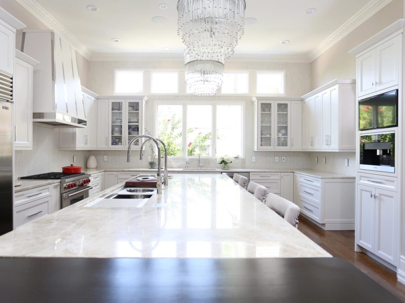 Large kitchen island with Galley Workstation, stainless Sub-Zero Wolf appliances, wood floors, white cabinets and island seating
