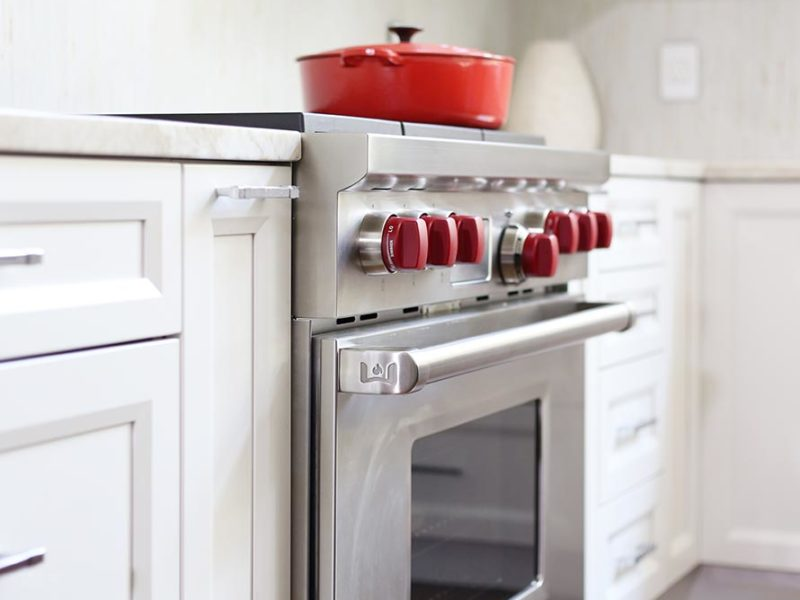 Timeless elegant south Tulsa kitchen with base pull-out storage, Wolf professional gas range, tile backsplash and glass panel wall cabinet storage