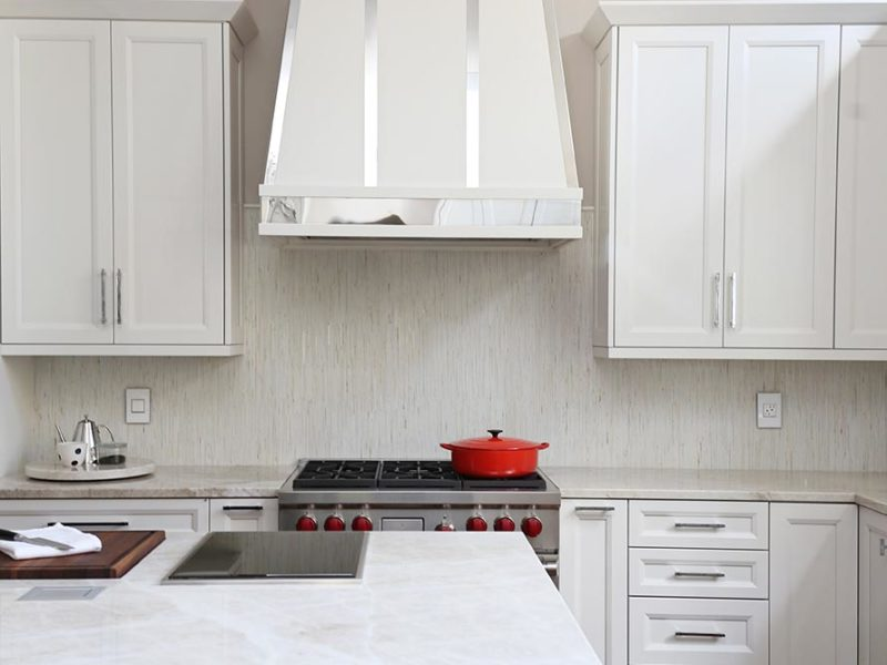 Timeless elegant south Tulsa kitchen remodel with decorative vent hood over a Wolf professional gas range, decorative tile backsplash and large island with two burner Wolf induction cooktop