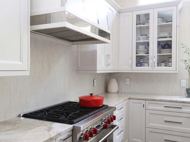 Timeless elegant south Tulsa kitchen with decorative vent hood, Wolf professional gas range, tile backsplash and glass panel wall cabinet storage