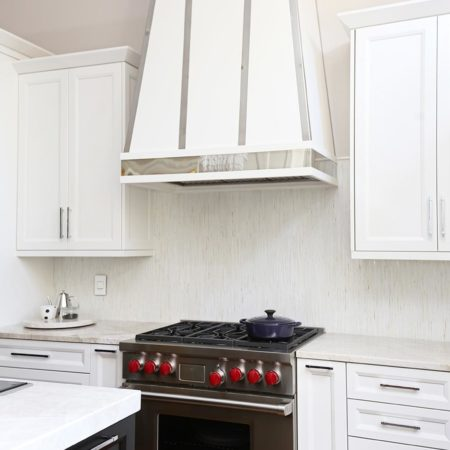 Tulsa kitchen with decorative vent hood, Wolf professional gas range, decorative tile backsplash and white cabinets wall storage with crown molding