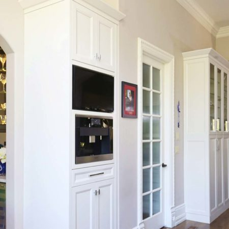 South Tulsa kitchen tall storage and Miele coffee center with inset tv and wood flooring